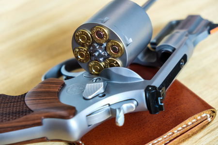 .357 .44 magnum revolver gun with bullet on wood background ammo object