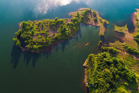 Dam with island green mountain forest blue water aerial view