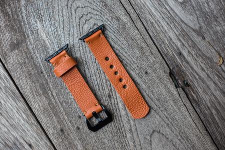 Handmade brown leather vintage watch strap craftsmanship on wood background