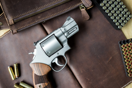 Revolver .44 magnum gun with jacket soft point (JSP) 240 grain bullet on leather background