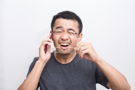 Smiling mustache asian man use smart phone felling surprise on white background, Business man