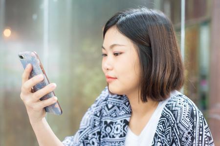 Beautiful asian women use smartphone in art cafe business communication