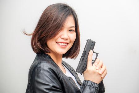 Smart beautiful women holding semi automatic gun piston on white background