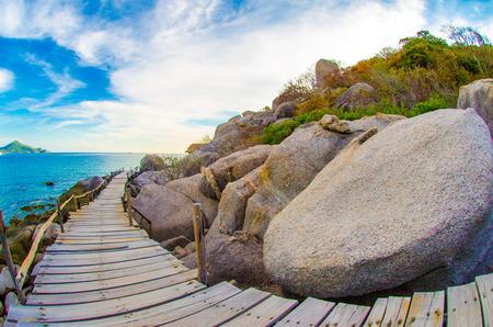 Wooden pathway sea coastline rocky beach sunset blue sky
