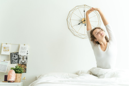 Women stretching on bed after wake up in morning, New life concept