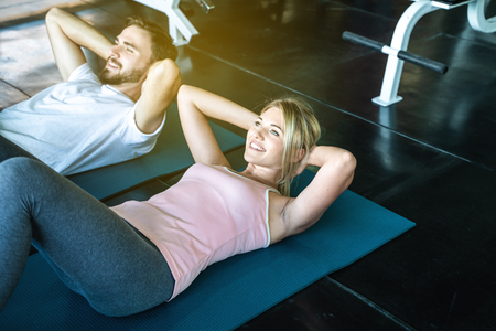 Couple of caucasian sport attractive man and women make sit up crunch exercise in gym Banco de Imagens