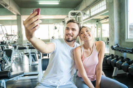 Caucasian sport couple take selfies photo after work out in gym, Couple in gym 免版税图像
