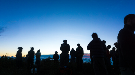 Silhouette group of people enjoying sunrise new year camping on mountain, New year new life