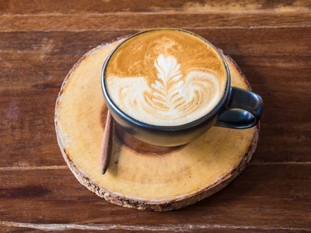 Hot latte art coffee in cup on wood table, Drink
