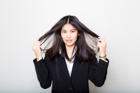 Business asian woman rubbing her hair feeling fatigue and headache afer work. Stress and frustration concept Stock Photo