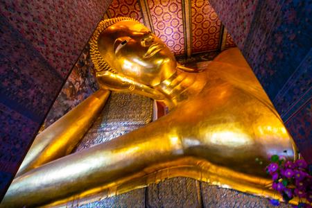 Gold statue reclining buddha indoor of Wat Pho buddhist temple Bangkok Thailand