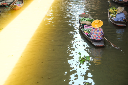 Floating market women in wooden boat trading food and beverage in morning, Thailand
