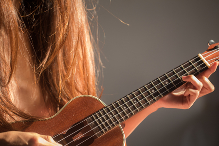 Women playing ukulele music with light of sun in morning