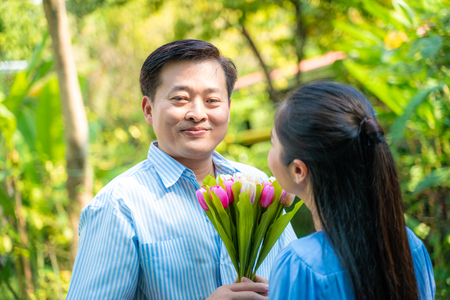 Happy mature couple talking together in green garden of home 写真素材