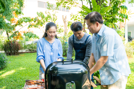 Group of people picnic party in home garden with bbq food drinking and eating