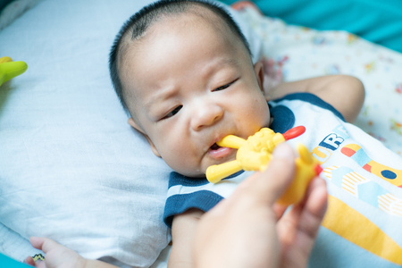 Infant baby boy chewing on teething with rubber bite toy