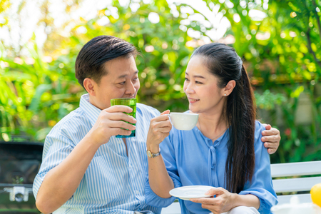 Happy mature couple talking together in green garden of home 스톡 콘텐츠