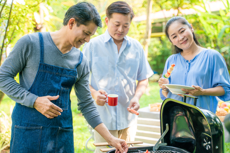 Group of people picnic party in home garden with bbq food drinking and eating Stock Photo