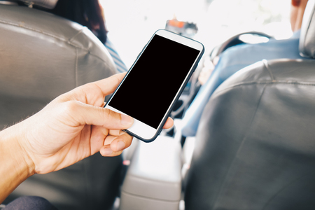 Blank screen smartphone use in hand sitting in taxi, Business travel