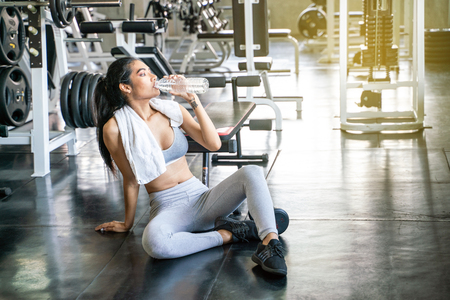 Sport women relaxing after weight training hold bottle of water and drinking, Wellbeing life