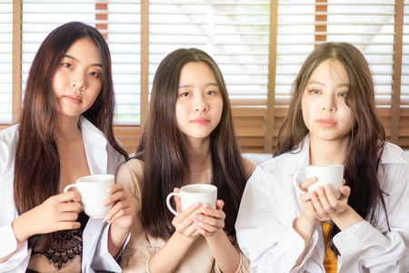 Group of asian girl having fun in home with coffee cup happy talking on couch at home Фото со стока