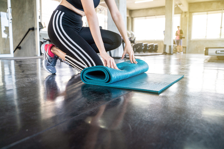Young sporty yoga woman rolling yoga mat in fitness gym