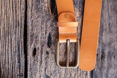 Brown leather belt handmade craftsmanship working on wood
