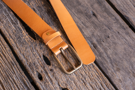 Brown leather belt handmade craftsmanship working on wood