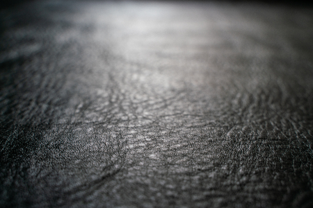 Black cow skin leather texture selective focus for put product, Leather background Фото со стока