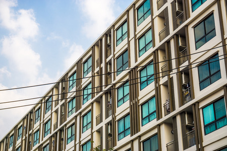 Modern condominiumblokgebouw met blauwe luchtwolk onroerendgoedindustrie