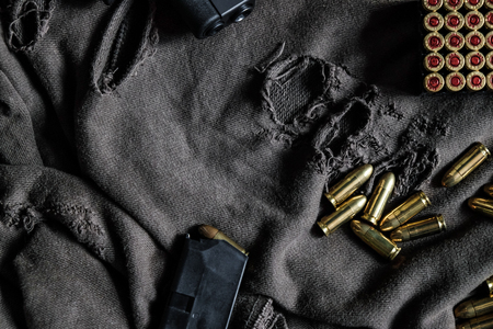 Polymer semi autometic 9mm gun with full metal jacket bullet on cloth background