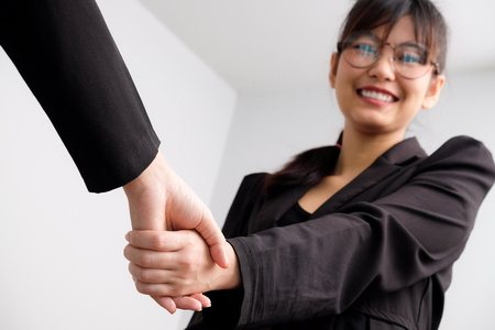 Business asian women shaking hand with partner job success on white background 写真素材