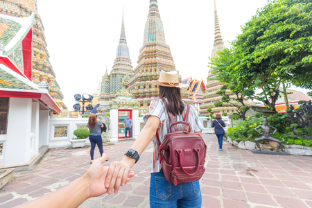 Beautiful tourist woman with backpack leading man hand travel in temple, Thailand