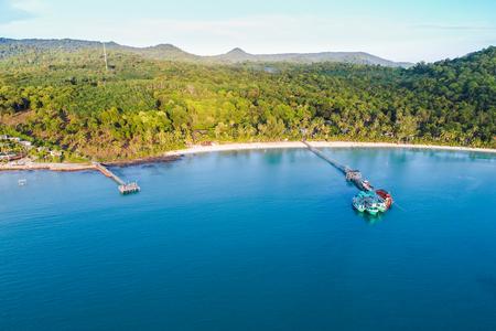 Molo di legno del mare con la barca sulla vista aerea della spiaggia