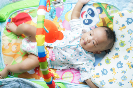 Adorable infant toddler boy playing toy on bed 4-6 month baby
