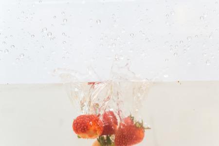 Fresh strawberry splash in water on white background, Fruit object 免版税图像