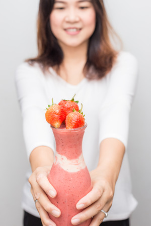 Smilling asian women with strawberry fruit smoothie bottle on white background