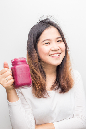 Beautiful healthy women drinking berry smoothie on white background