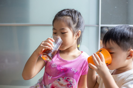 Funny child boy and girl drinking sweet ice drink in cozy room Stock Photo