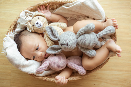 Infant baby boy lying in wood basket eat milk with many doll Stockfoto