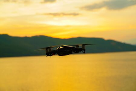 Silhouette drone flying over lake sunset colorful sky