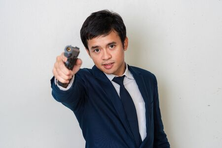 Business man in suit holding hand gun on white background, Spy concept