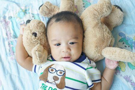 Niño sonriente niño asiático acostado en la cama enjy con muñeca