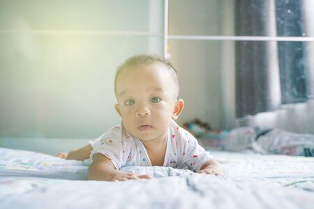 Funny baby boy crawling on blanket in bed room 6 month son 写真素材