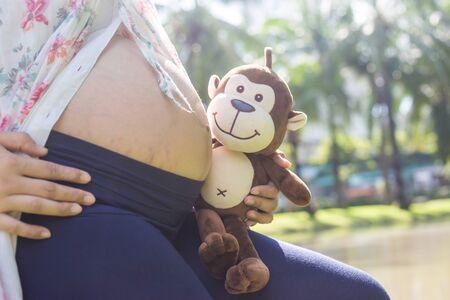 Asian pregnant women posing in city public green park enjoy nature