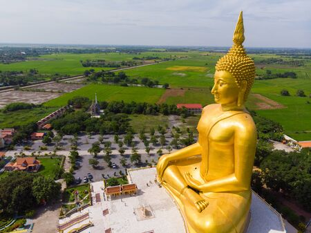 Golden buddha statue in buddhism temple with rice plantation aerial view 写真素材