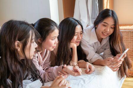 Women friend group use smartphone lying on bed meeting friendship Foto de archivo