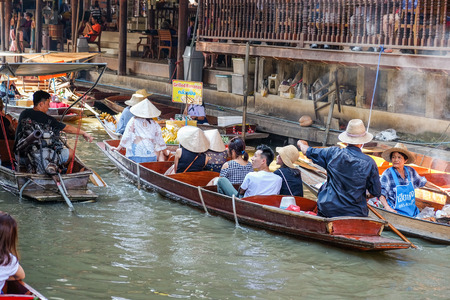BANGKOK – MARCH 25: Boat service with tourist people at Damnoen Saduak floating market on March 25, 2017 in Bangkok. Traditional popular place of buying and selling still practiced in Damnoen Saduak canals of Thailand.