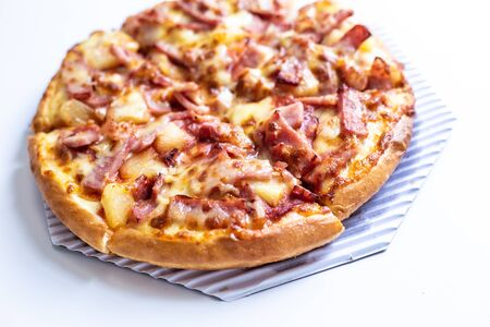 pizza hawaiian with ham cheese close up on white background