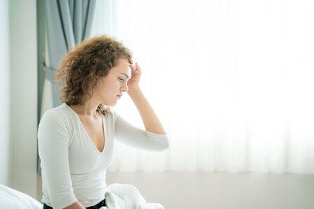 Jonge vrouwen die op bed zitten, worden wakker met haar hoofd en voelen zich misselijk, Hoofdpijnvrouwen op bed